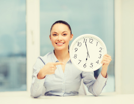 the end of time: business, office, school and education concept - attractive businesswoman pointing finger to clock