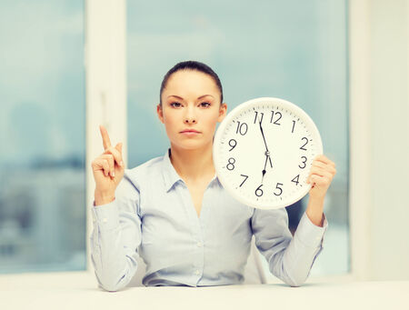 hurry up: business, office, school and education concept - attractive businesswoman showing clock with finger up