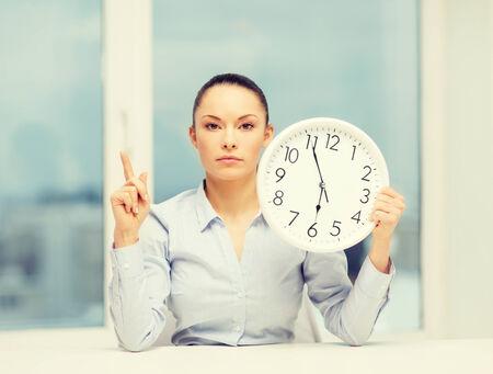 concept d'affaires, de bureau, d'école et de l'éducation - horloge de projection de femme d'affaires attrayant avec le doigt vers le haut