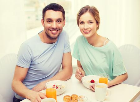familia comiendo: comida, hogar, pareja y concepto de la felicidad - sonriente pareja desayunando en casa