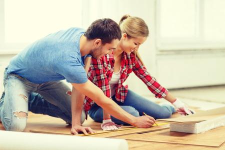 parquet flooring: repair, building and home concept - smiling couple measuring wood flooring