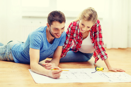 homeowner: repair, building, renovation and home concept - smiling couple looking at blueprint at home