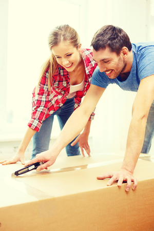 moving activity: repair, building and home concept - smiling couple opening big cardboard box