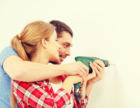 repair, interior design, building, renovation and home concept - smiling couple drilling hole in wall at home photo
