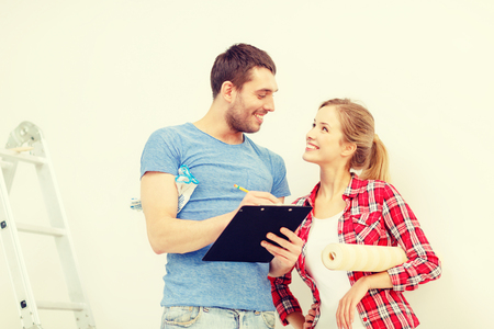 renovating: repair, building and home concept - smiling couple with clipboard, wallpaper roll and ladder