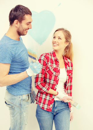 mischief: repair, building and home concept - smiling couple painting small heart on wall at home Stock Photo