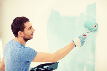 painting and decorating: repair, building and home concept - smiling man painting wall at home