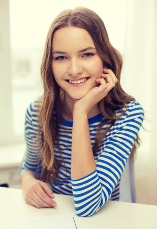 education and home concept - smiling teenage girl with notebook at home photo