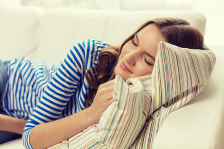 sleeping rooms: home and happiness concept - smiling teenage girl sleeping on sofa at home