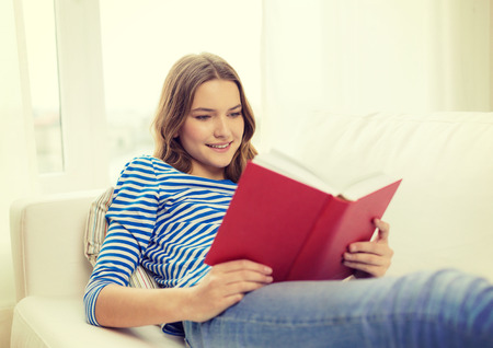 resting: leisure, education and home concept - smiling teenage girl reading book and sitting on couch at home Stock Photo