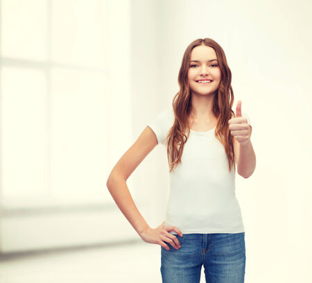 advertising space: t-shirt design concept - smiling teenager in blank white t-shirt showing thumbs up