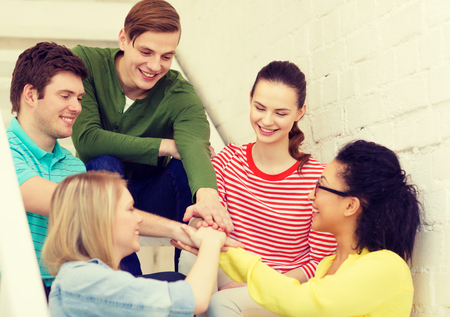 school friends: education and happiness concept - smiling students with hands on top of each other sitting on staircase
