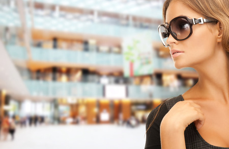 eyewear: people, fashion, shopping, eyewear and style concept - beautiful woman in shades over mall background