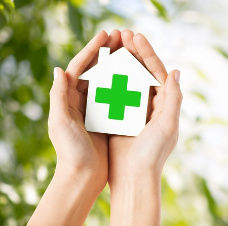 eradication: care, help, charity and people concept - close up of hands holding white paper house with green cross sign over natural background