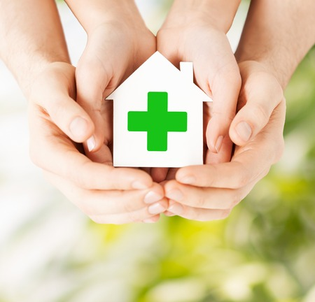 eradication: care, help, charity and people concept - close up of hands holding white paper house with green cross sign