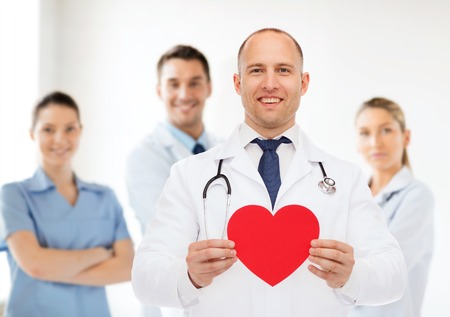 cardiologist: medicine, profession, charity and healthcare concept - smiling male doctor with red heart and stethoscope over group of medics