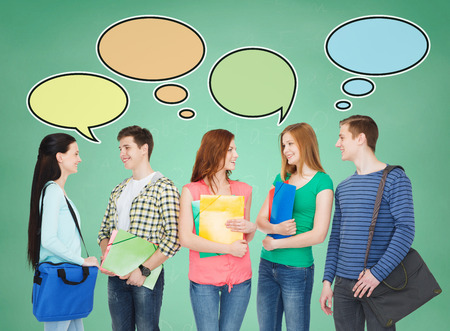 school, education, communication and people concept - group of smiling teenagers with folders and school bags talking over green board background with text bubbles photo