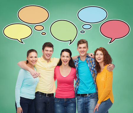 school, education, communication and people concept - group of smiling teenagers over green board background with text bubbles photo