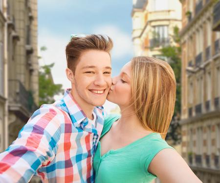 to kiss: los viajes, el turismo, las vacaciones de verano, la tecnolog�a y el concepto de amor - feliz pareja teniendo Autofoto con smartphone o c�mara y un beso sobre la ciudad de la calle de fondo