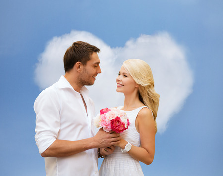 holidays, love, people and dating concept - happy couple with bunch of flowers over blue sky and heart shaped cloud background photo