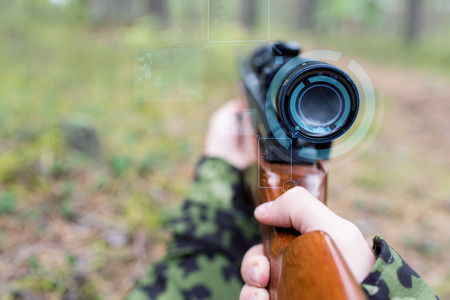 corps: hunting, war, army, technology and people concept - close up of young soldier or sniper hands holding gun with virtual screen projection and aiming in forest Stock Photo