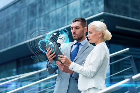 business, partnership, technology and people concept - businessman and businesswoman working with tablet pc computer and globe hologram on city street photo