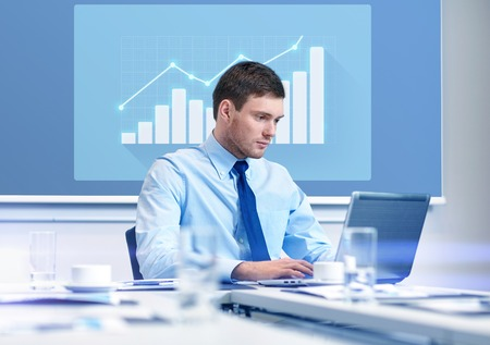 virtual office: business, people and work concept - businessman with laptop computer and growth chart on virtual screen in office