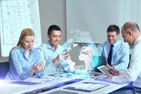 bedrijfsleven, mensen, samenwerking en technologie concept - lachende business team met gadgets en bol hologram bijeenkomst in het kantoor