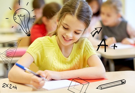 education, elementary school, learning and people concept - group of school kids with notebooks writing test in classroom over doodles Stockfoto