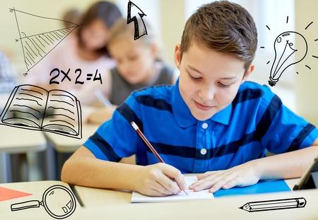 学校のグループがペンとノートの落書きを教室でテストを書く子供教育、小学校、学習、人々 のコンセプト-