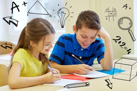 education kids: education, elementary school, learning and people concept - group of school kids with pens and notebooks writing test in classroom with doodles
