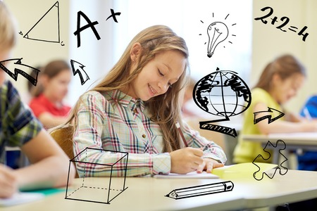 education, elementary school, learning and people concept - group of school kids with notebooks writing test in classroom over doodles Stock Photo