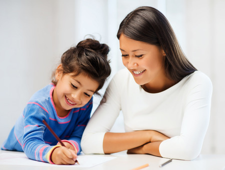 mummy: family, children and happy people concept - mother and daughter drawing Stock Photo