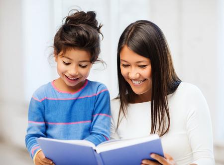 niños leyendo: familia, los niños, la educación, la escuela y la gente feliz concepto - madre e hija con el libro