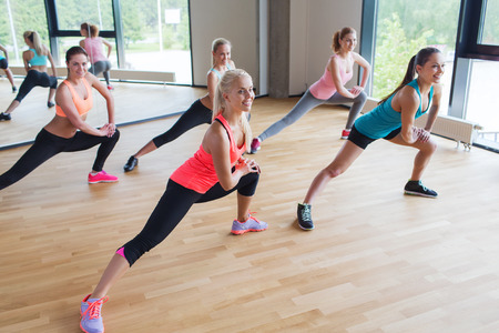 aerobics class: fitness, sport, training, people and lifestyle concept - group of women making lunge exercise in gym