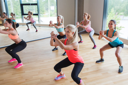 squats: fitness, sport, training, people and lifestyle concept - group of women making squats in gym Stock Photo