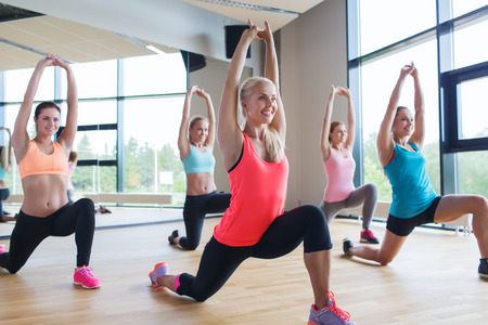 athletic women: fitness, sport, training, people and lifestyle concept - group of women making lunge exercise in gym