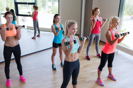 flexing: fitness, sport, people and lifestyle concept - group of women exercising with dumbbells in gym