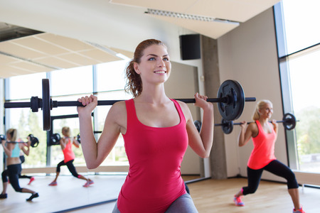 lifting weights: fitness, sport, training, gym and lifestyle concept - group of women excercising with bars in gym Stock Photo