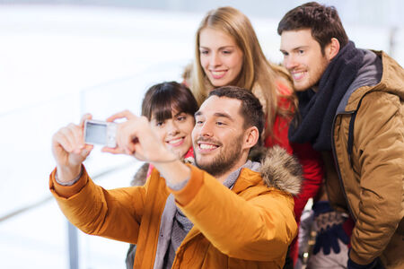 ice arena: people, friendship, technology and leisure concept - happy friends taking selfie with digital camera on skating rink Stock Photo
