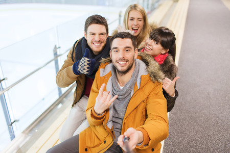 friends happy: people, friendship, technology and leisure concept - happy friends taking selfie with camera or smartphone and selfie stick on skating rink
