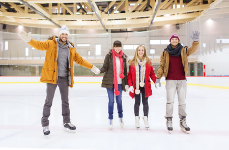 ice arena: people, friendship, gesture, sport and leisure concept - happy friends waving hands on skating rink