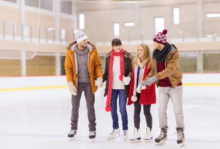 ice arena: people, friendship, sport and leisure concept - happy friends on skating rink
