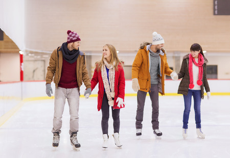 skaters: people, friendship, sport and leisure concept - happy friends on skating rink