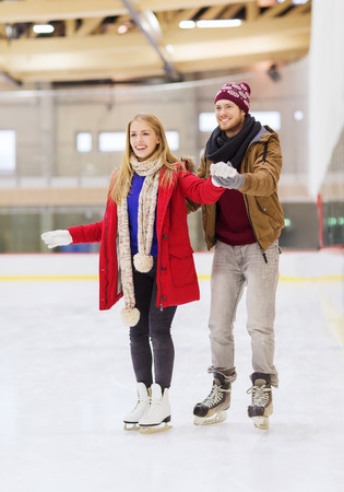 iceskates: people, friendship, sport and leisure concept - happy couple on skating rink Stock Photo