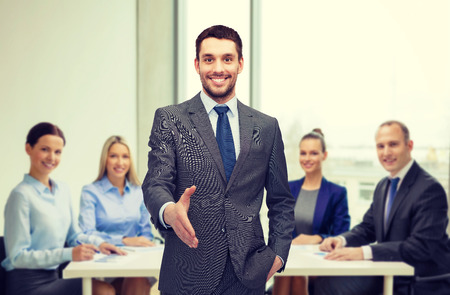shaking hands: business and office concept - handsome businessman with open hand ready for handshake Stock Photo