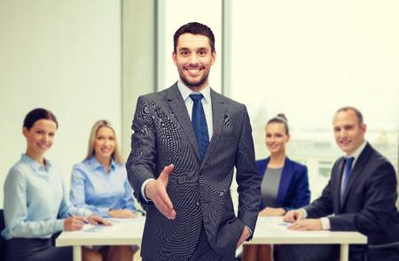 bienvenidos: comercial y de oficinas concepto - apuesto hombre de negocios con la mano abierta listo para apret�n de manos