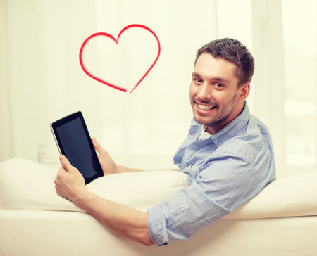 finding love: technology, home and lifestyle concept - smiling man working with tablet pc computer at home
