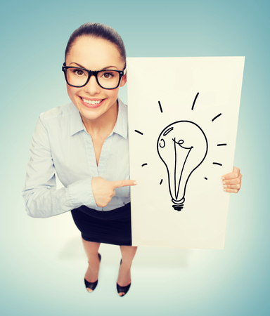 business and advertisement concept - smiling businesswoman in eyeglasses pointing finger to white board with light bulb photo