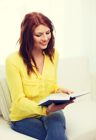 leasure: leasure and home concept - smiling teenage girl reading book and sitting on couch at home